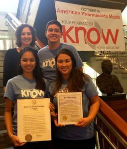 Dr. Macary Marciniak and pharmacy students Evan Colmenares, Trang Leminh, and Jenny Levine with the proclamations from Mayor Kleinschidt and Governor McCrory.