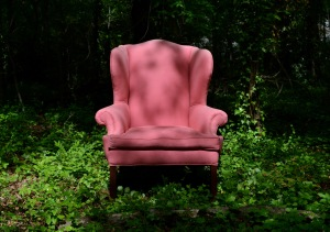 Here is a comfy pink chair in the forest a person might sit in if they were taking a break.