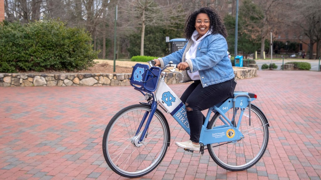 Gaby Behailu, a Healthy Heels communication intern, shows off Tar Heel Bikes in SASB Plaza.