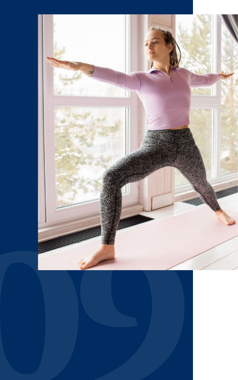 Woman does warrior pose in yoga in front of windows