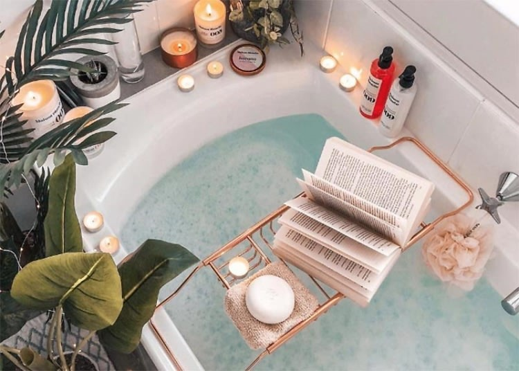 A bath with bubbles, candles, soap, and a book
