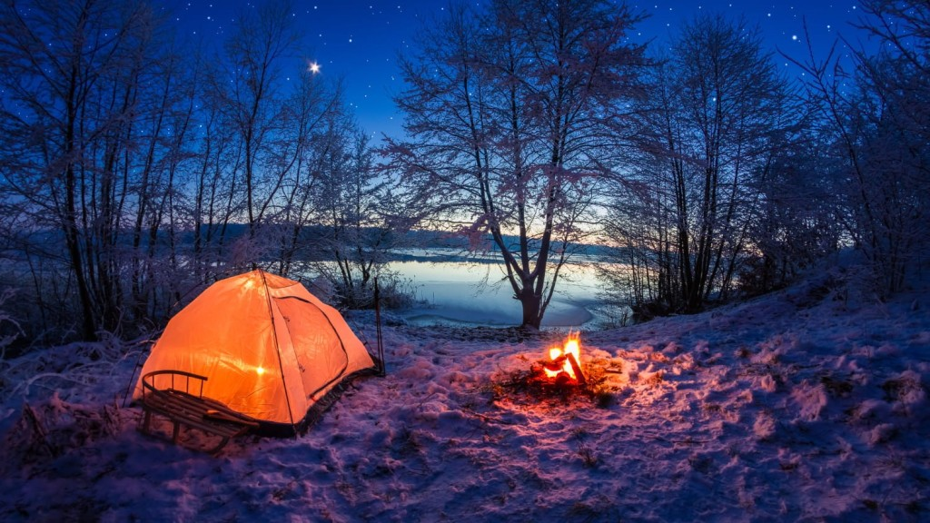 Glowing tent and fire at night by a lake