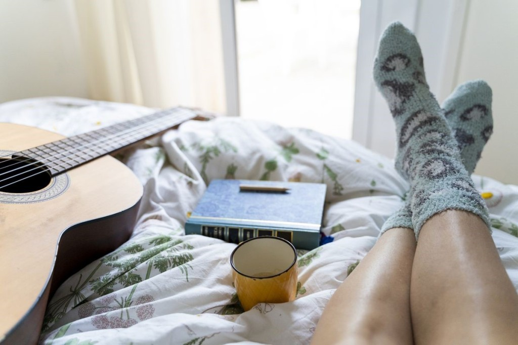 A person in socks over a bedspread lays next to a book, pencil, mug, and guitar