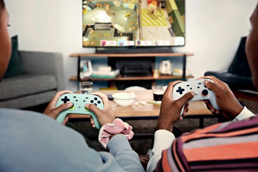 Two people with gaming consoles play a video game together