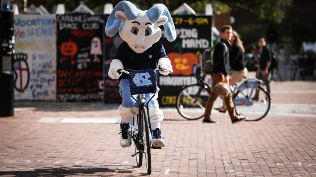 Rameses bikes on a Tar Heel Bike in the Pit while students look on behind him