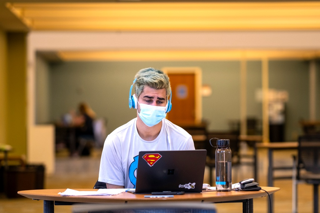 Student studying in the library with a superman sticker on his laptop and a tired look on his face