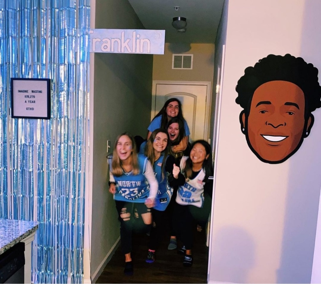 UNC students wearing UNC gear with blue streamers, a UNC basketball player face cut-out and Franklin Street sign in their hallway.