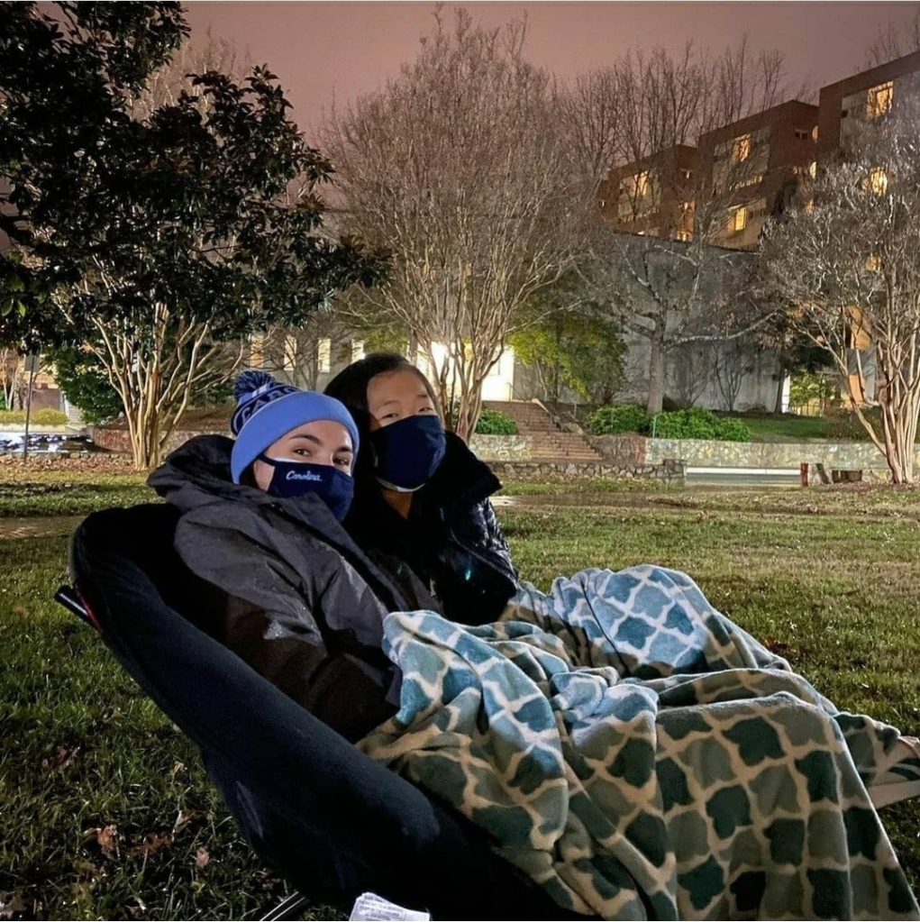 UNC students in Carolina gear sit outside under a blanket during the last UNC game against Duke